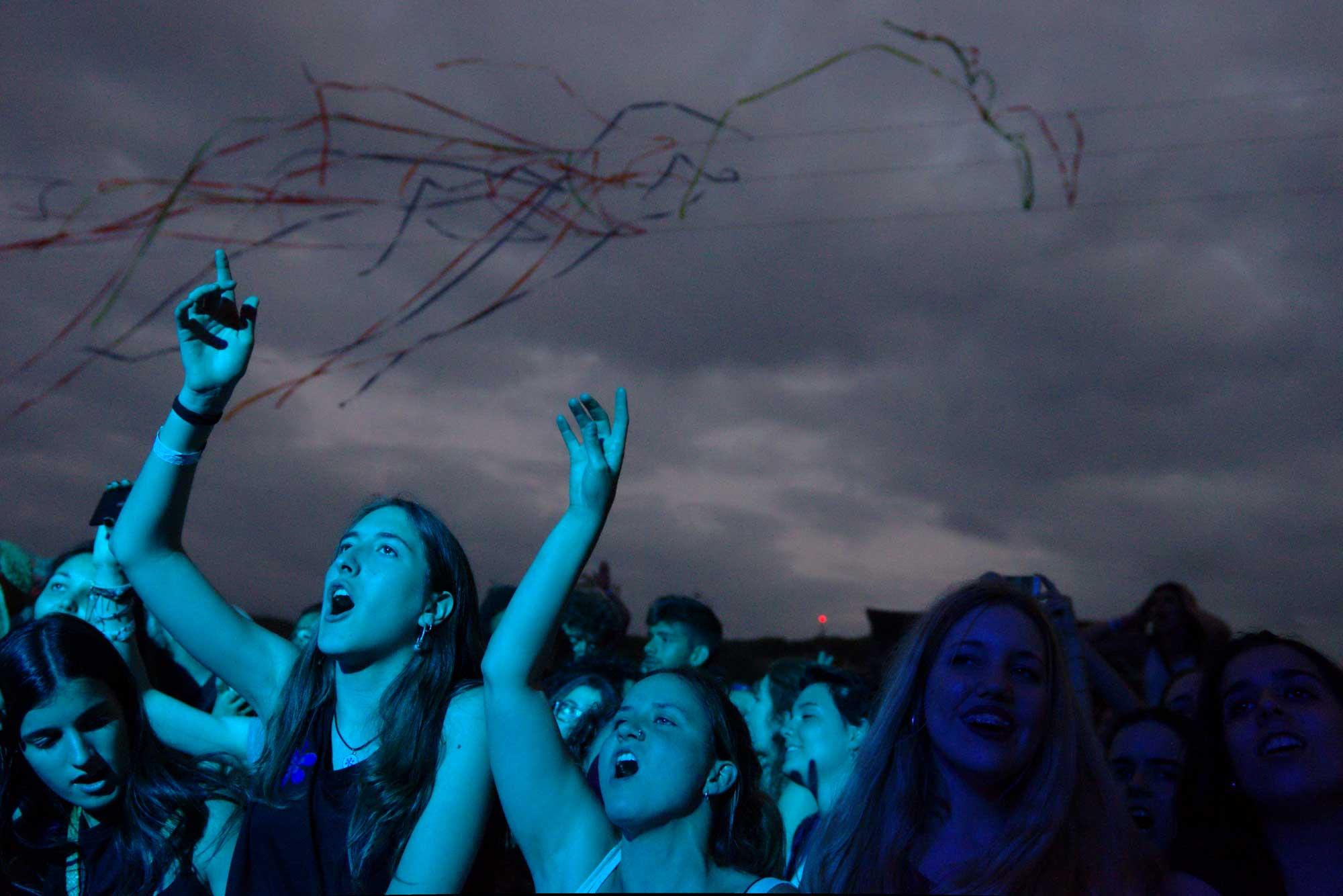 Públic durant l'actuació d'Els Catarres, l'última del Canet Rock 2016, veient com torna a sortir el sol després de 12 hores consecutives de concerts. Al fons, confetti penjant d'un cables.