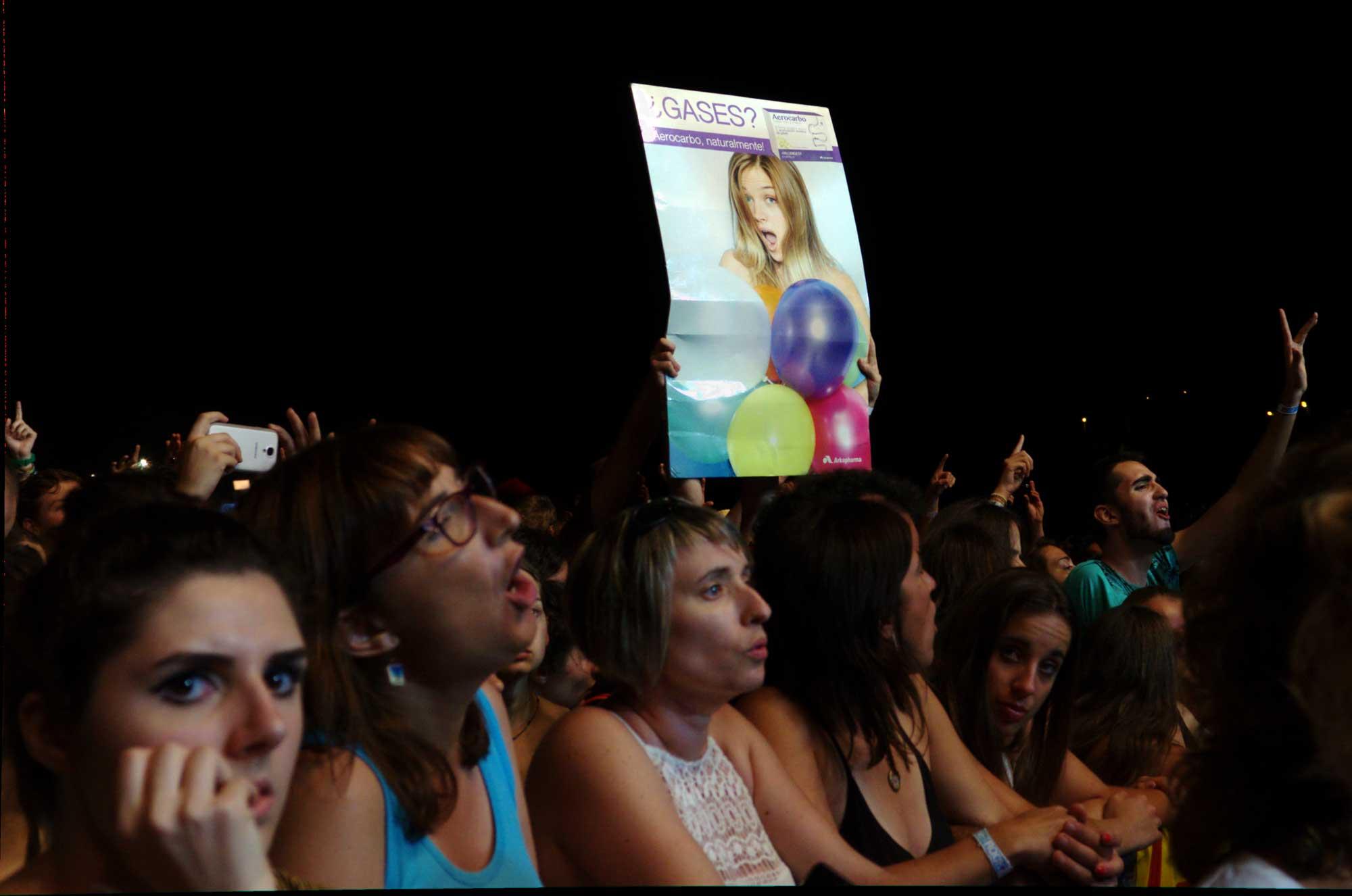 Públic mostrant un cartell farmaceútic d'un mètode per aliviar els gassos durant un concert d'Els Pets al Canet Rock 2016.