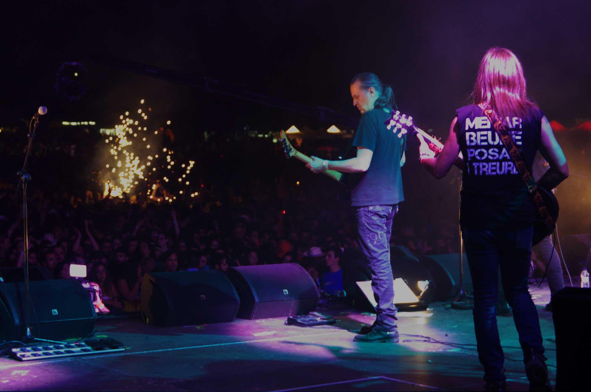 Los Guardians del Pont actuant al Canet Rock amb Josep Maria Corominas, ex-Sangtraït, com a convidat, vistos des del fons de l'escenari. Al fons el públic i espurnes de focs d'artifici.